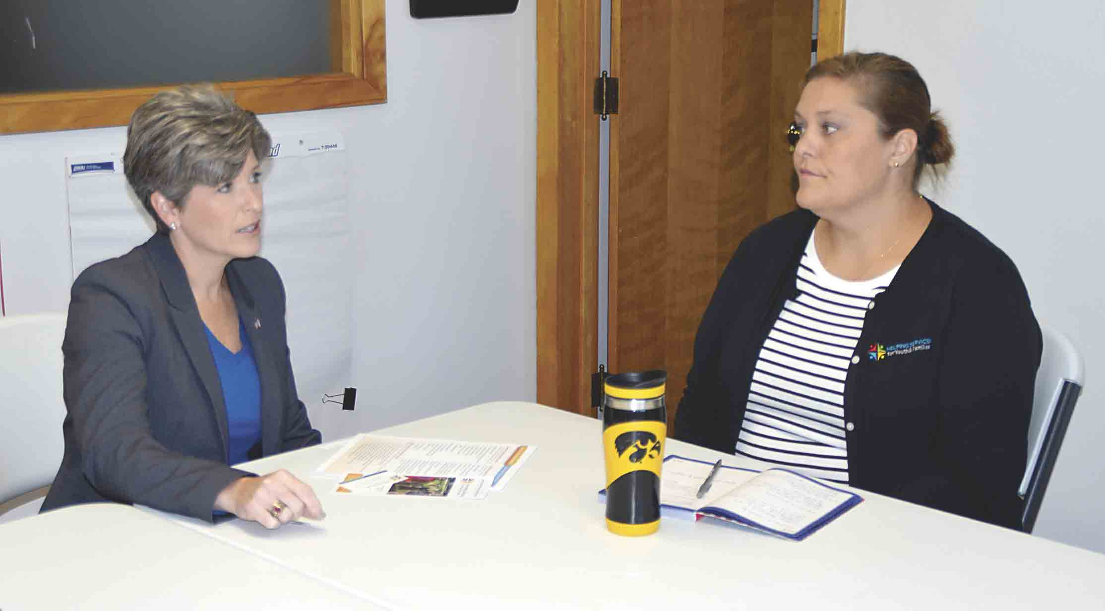 Stacie Schroeder (right), TigerHawk Connections Learning Center program director, speaks with U.S. Senator Joni Ernst about the after school program that is funded by a federal grant, and the different ways the program supports children learning after school.  Chris DeBack photos...