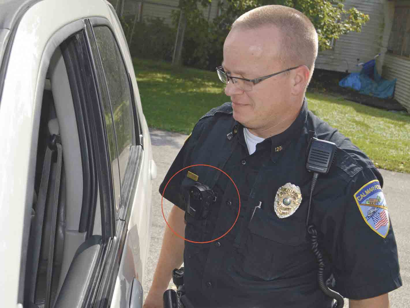 On a routine traffic stop, Calmar Police Chief Joe Ward approaches a vehicle while wearing a body-worn camera (circled). In 2014, the local police force became the first law enforcement agency in Winneshiek County to begin using the small cameras while on duty. Both officers on the force,...
