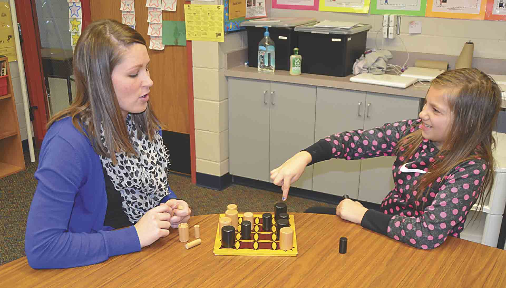 North Fayette Valley Community Coalition mentor Mollie Franzen (left) enjoys spending quality time with her mentee, Valley Elementary third-grader Haley Voshell. Here, Haley explains her strategy to Franzen while the two play a board game together.Mentoring 'so gratifying...