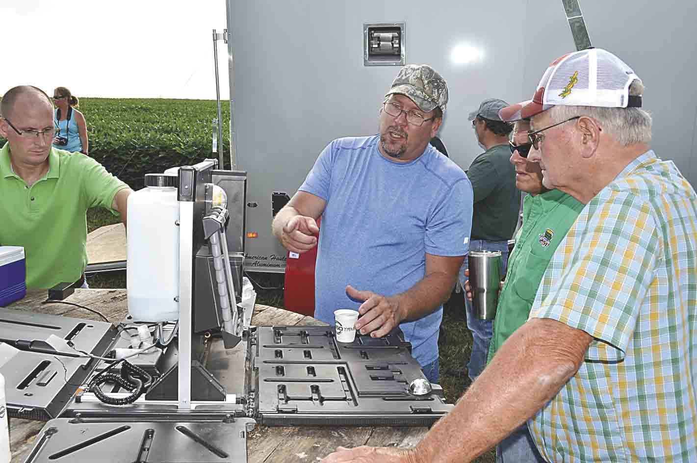 NRCS employee Roger Erickson (center) discusses a tool used for soil and water analysis during a cover crop field day just outside West Union on Tuesday, Aug. 16. The device can test for phosphorus, nitrates, pH (acidity) and sulphur. Listening (at right) are Tim Recker and Bob Deering. (...