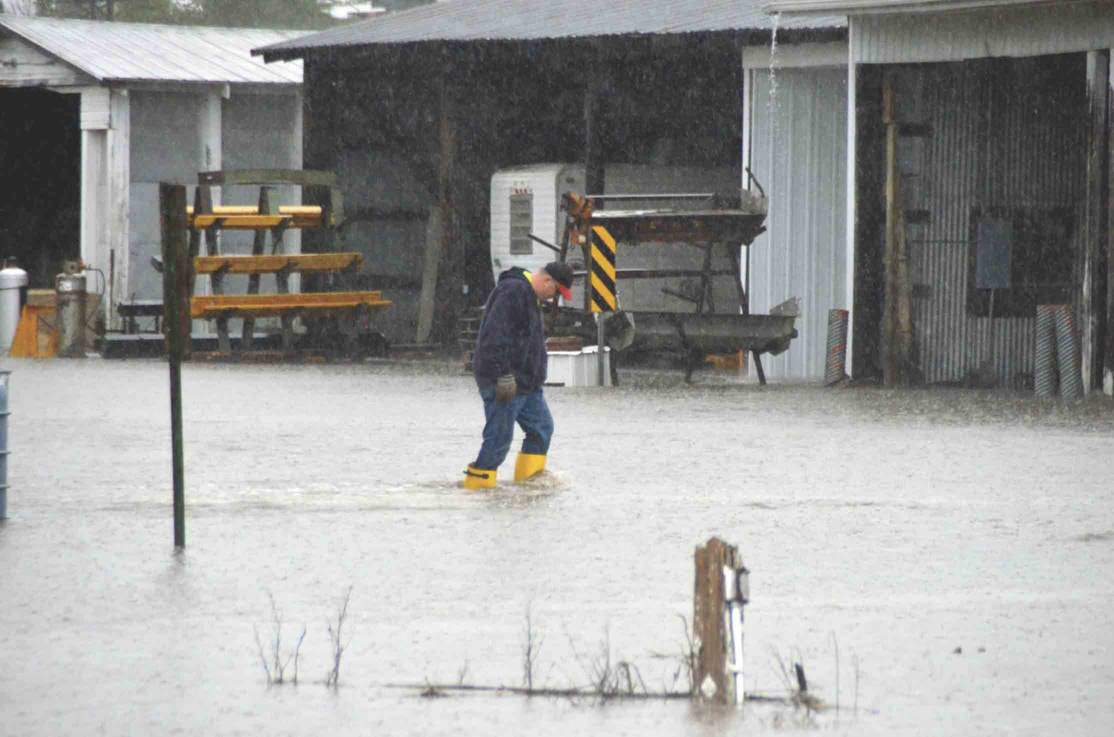 Tim Brugman, Fayette County Secondary Roads employee, trudges through water at the County Shop in West Union. Instead of concentrating all efforts on closing roads, the shop employees were busy moving equipment and other items out of the flooded areas of the shop.Northeast Iowa...